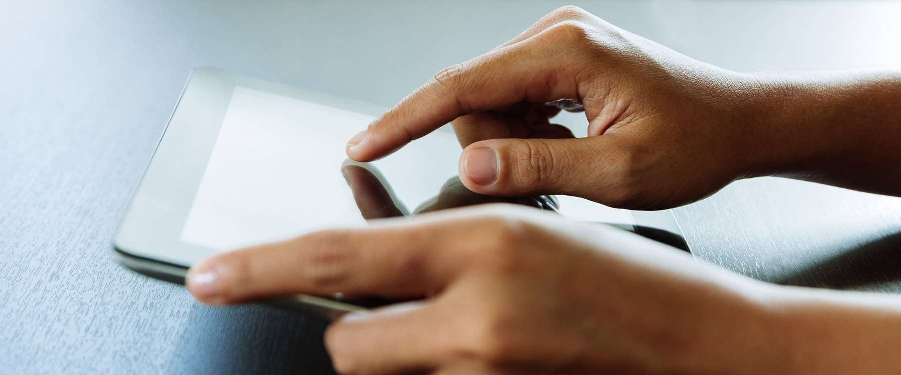 close up of hands using a tablet