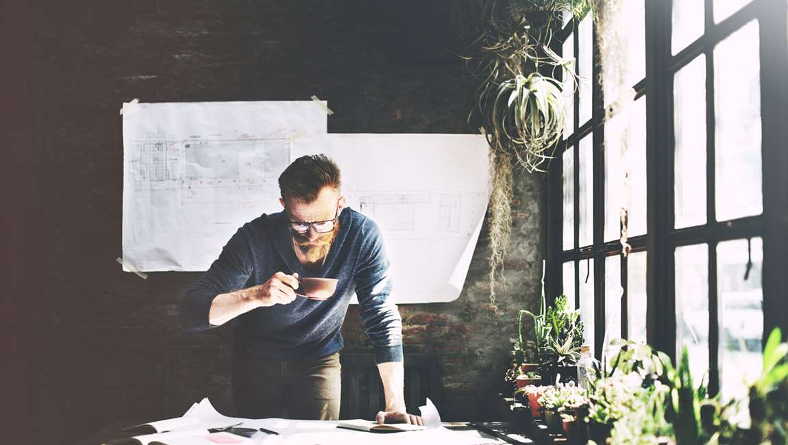 man looking at blueprints and drinking coffee