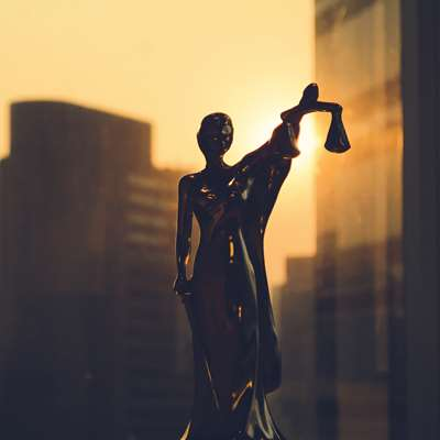 small statue of lady justice in window