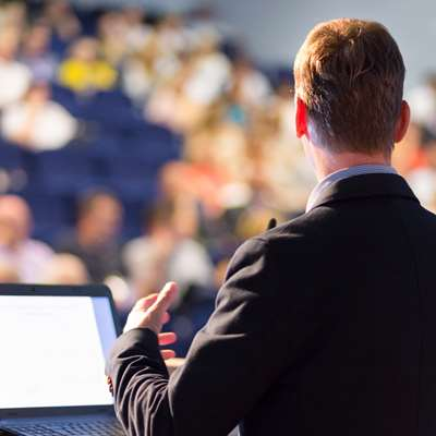 over shoulder of speaker in lecture hall