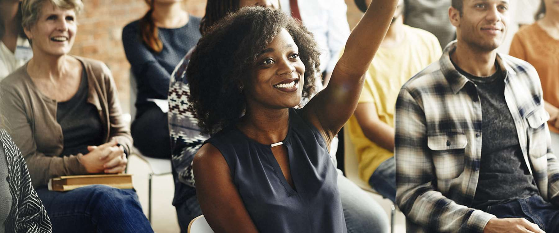 woman raising hand in group